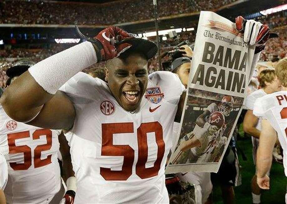 Alabama defensive lineman Alphonse Taylor (50) holds up a newspaper after the BCS National Championship college football game Monday, Jan. 7, 2013, in Miami. Alabama won 42-14. (AP Photo/David J. Phillip) Photo: ASSOCIATED PRESS / AP2013