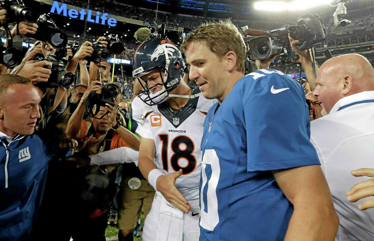 Broncos quarterback Peyton Manning (18) shakes hands with his brother Eli after Sunday's game. The Broncos won 41-23.