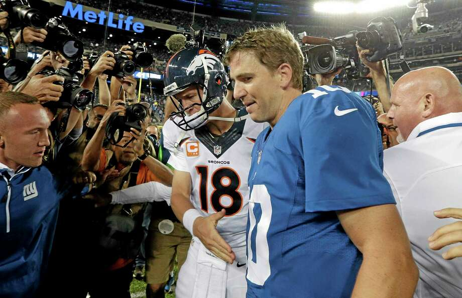 Broncos quarterback Peyton Manning (18) shakes hands with his brother Eli after Sunday's game. The Broncos won 41-23. Photo: Frank Franklin II — The Asssociated Press  / AP