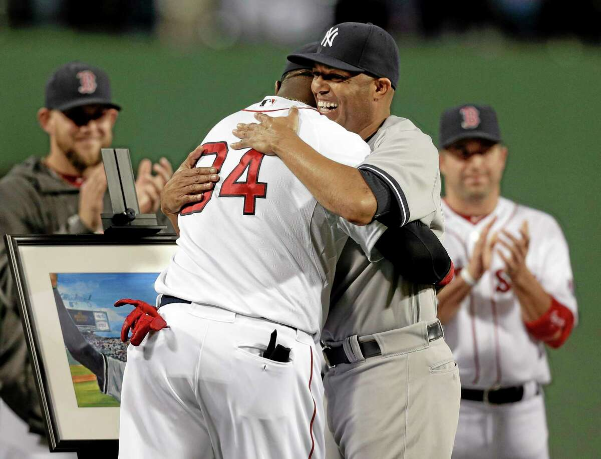 Yankees closer Mariano Rivera, right, hugs David Ortiz during a tribute before Sunday's game.