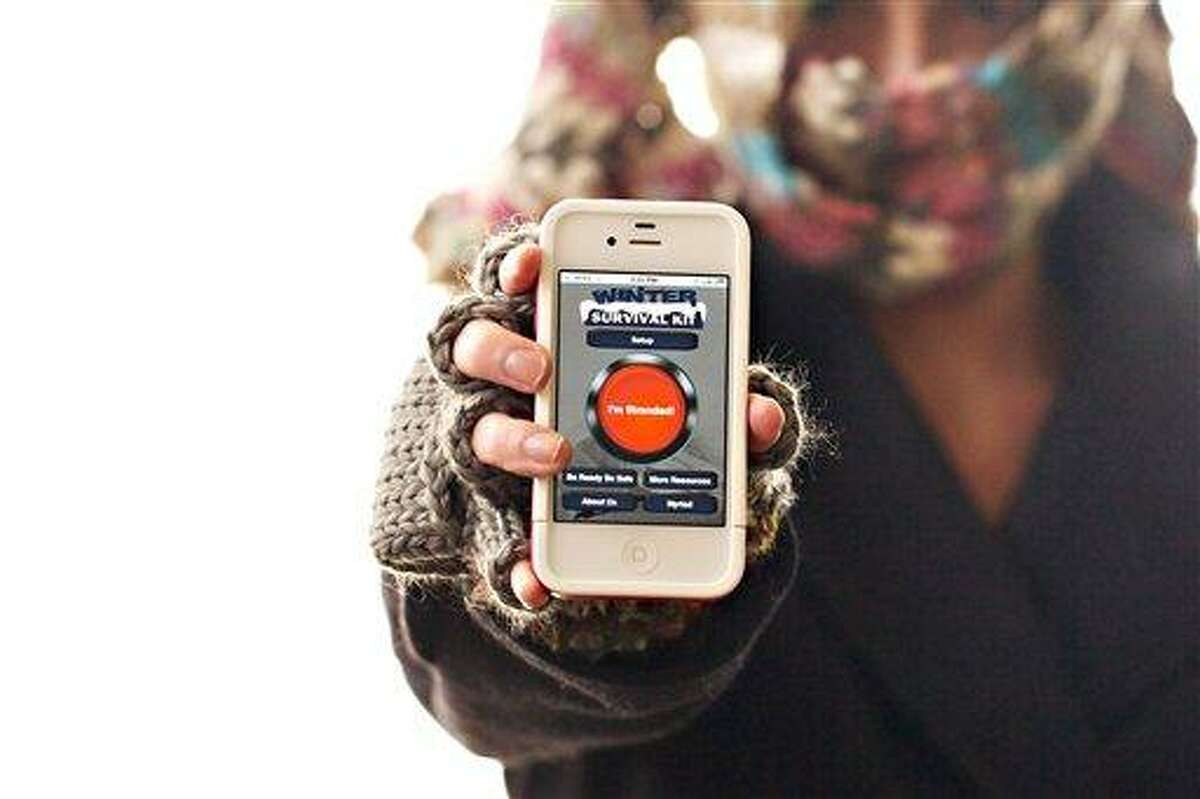 In this Dec. 29, 2011, photo, a woman poses with a smart phone displaying the Winter Survival Kit, a smart-phone application developed by Myriad Devices, a startup company in the North Dakota State University's research and technology park, in Sioux Falls, S.D. Associated Press