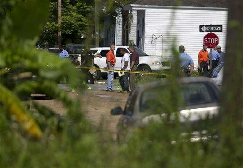 New Orleans Police investigate shooting at the intersection Frenchman Street at N. Villere on Mother's Day in New Orleans, Sunday May 12, 2013. Gunmen opened fire on dozens of people marching in a Mother's Day neighborhood parade in New Orleans on Sunday, wounding at least 17, police said. (AP Photo/Doug Parker) Photo: ASSOCIATED PRESS / AP2013