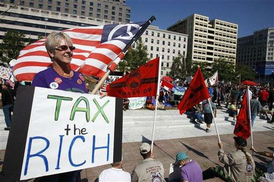 "In this Oct. 6, 2011, file photo, Carol Gay, of Brick, N.J., holds a sign saying ""Tax the Rich,"" as several groups including the Peoples Uprisings, October 2011 Coalition, and Occupy DC, ""occupy"" Freedom Plaza in Washington. Absent a magic potion or explosive economic growth, it was all but inevitable President Barack Obama would have to break some of his campaign promises to keep others. If there's one thing that distinguished them besides their ambition, it was their incompatibility. Taxes are at the center of every major budget fight gripping Washington. Democrats and Republicans simply do not agree on whether taxpayers should be asked to shell out more in order to reduce government borrowing. That?s why Congress and the White House couldn?t agree on a plan to avoid automatic spending cuts. (AP Photo/Jacquelyn Martin, File) Photo: AP / AP"