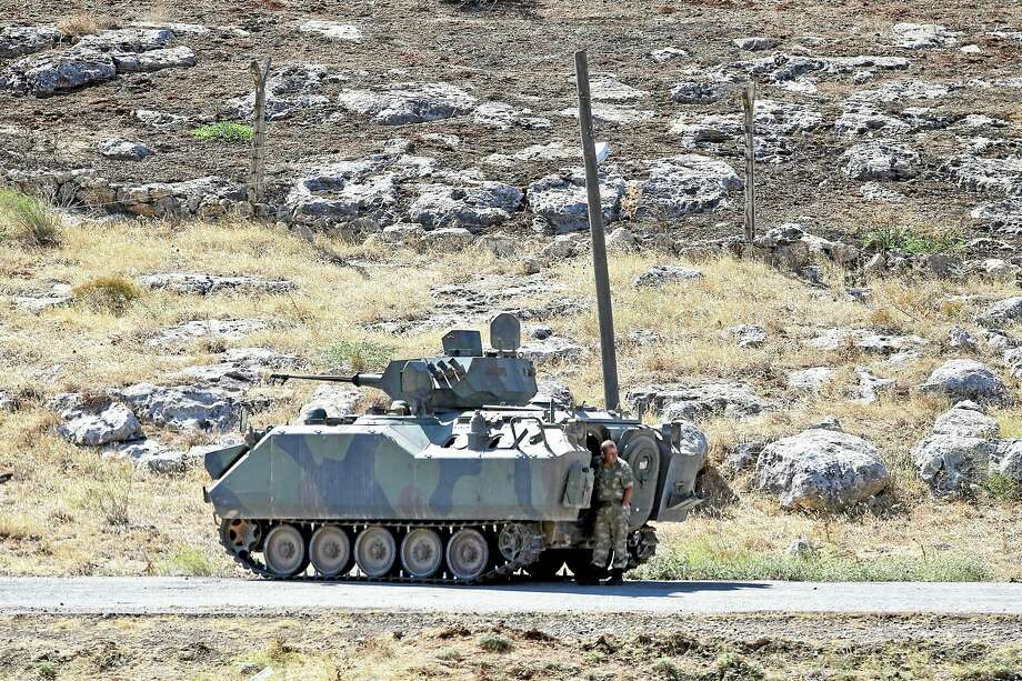 A Turkish soldier stands by a tank as he patrols the border with Syria, near Cilvegozu, Turkey, Wednesday, Sept. 11, 2013. U.S. President Barack Obama conditionally endorsed a Russian offer for international inspectors to seize and destroy deadly chemical weapons in Syria as efforts to avert retaliatory U.S. missile strikes shift from Washington to the United Nations. (AP Photo/Gregorio Borgia) Photo: AP / AP