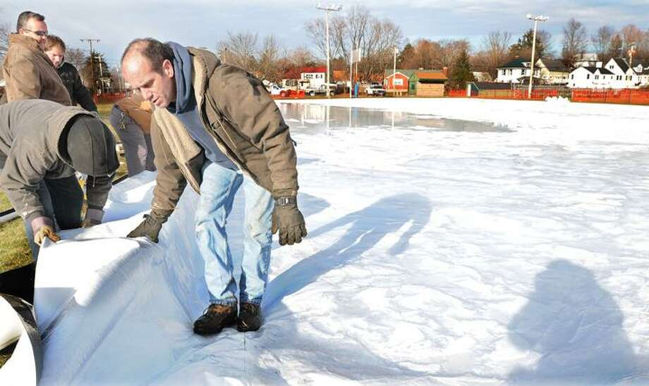 The Middletown Press  1.4.12  Damian Renzello, at right, owner of Porta-Rinx of East Montpelier, Vermont directs Jim Sweeney, an employee of the Middletown Parks & Recreation Department as he installs the PVC pipe frame to the portable ice rink at Pat Kidney Field Wednesday afternoon. Renzello and a crew from the Parks & Recreation added concrete blocks to level the rink from east to west. Renzello said the 100 x 200 olympic-sized rink made from 12-millimeter plastic liner cost $8300 and needs a temperatures of18 degrees to make ice. To buy a print of this photo and more, visit the photo gallery at www.middletownpress.com / TheMiddletownPress