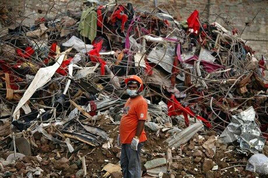 A Bangladeshi rescuer stands amid the rubble of a garment factory building that collapsed on April 24 as they continue searching for bodies in Savar, near Dhaka, Bangladesh, Sunday, May 12, 2013. Search teams resumed their rain-interrupted work Sunday as the death toll from the collapse continued to climb past 1,100. (AP Photo/A.M. Ahad) Photo: AP / AP