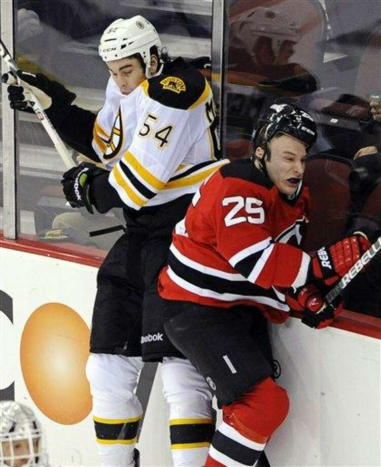 Boston Bruins' Adam McQuaid (54) and New Jersey Devils' Cam Janssen (25) collide along the boards during the third period of an NHL hockey game Wednesday, Jan. 4, 2012, in Newark, N.J. The Bruins won 6-1. (AP Photo/Bill Kostroun) Photo: AP / FR51951 AP