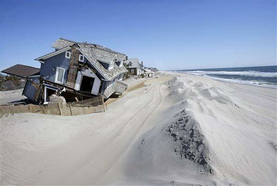 Homes severely damaged last October by Superstorm Sandy, are seen along the beach Thursday, April 25, 2013, in Mantoloking, N.J. Six months after Sandy devastated the Jersey shore and New York City and pounded coastal areas of New England, the region is dealing with a slow and frustrating, yet often hopeful, recovery. (AP Photo/Mel Evans) Photo: AP / AP