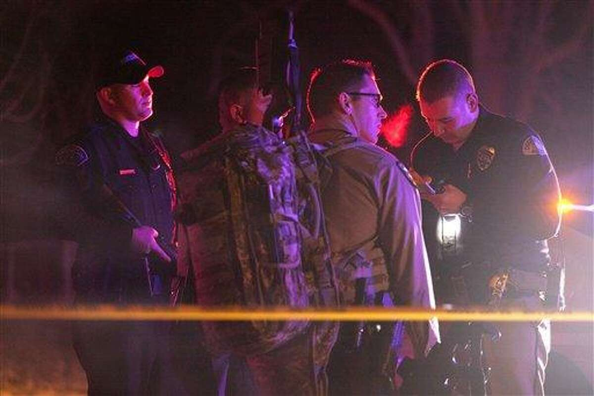 Police officers and emergency crew are seen near 3268 Jackson St., in Ogden, Utah, where 6 police officers were shot, including those from the Weber-Morgan Narcotics Strike Force and the Ogden Police Department, while serving a warrant Wednesday. The suspect was also shot. Associated Press