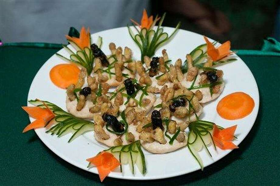 This undated photo provided by the United Nations Food and Agriculture Organization (FAO) shows a plate with insects during an insect cuisine competition at an unknown location in Laos. The U.N. has new weapons to fight hunger, boost nutrition and reduce pollution, and they might be crawling or flying near you right now: edible insects. The Food and Agriculture Organization on Monday, May 13, 2013, hailed the likes of grasshoppers, ants and other members of the insect world as an underutilized food for people, livestock and pets. A 200-page report, released at a news conference at the U.N. agency's Rome headquarters, says 2 billion people worldwide already supplement their diets with insects, which are high in protein and minerals, and have environmental benefits.  (AP Photo/Thomas Calame, FAO, ho) Photo: AP / FAO