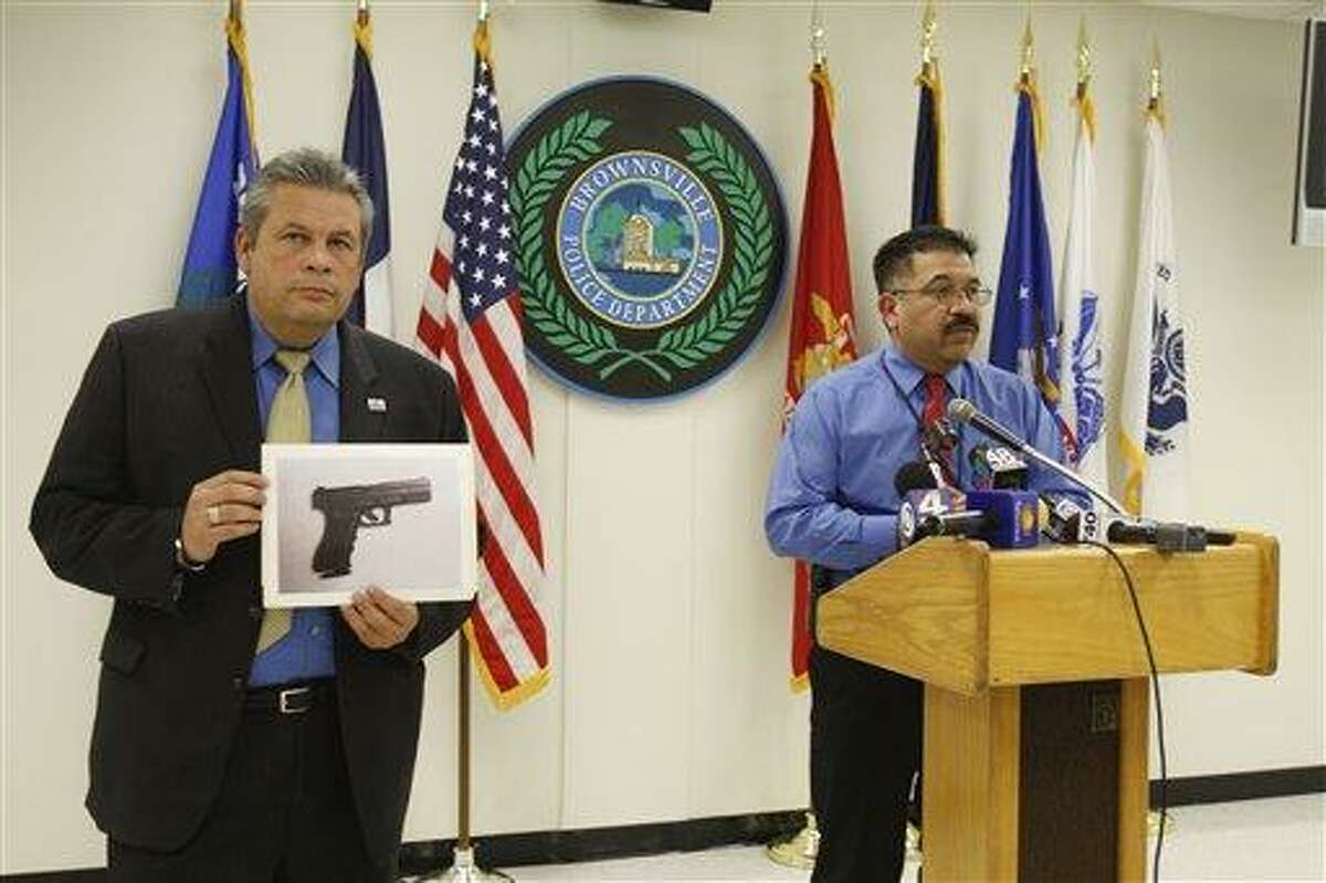 Brownsville city manager Charlie Cabler, left, holds up a photo of the carbon dioxide powered pellet handgun Jaime Gonzalez, 15, was holding at the time he was shot by police at Cummings Middle School as Police Chief Orlando Rodriguez speaks during a news conference Wednesday in Brownsville, Texas. Associated Press