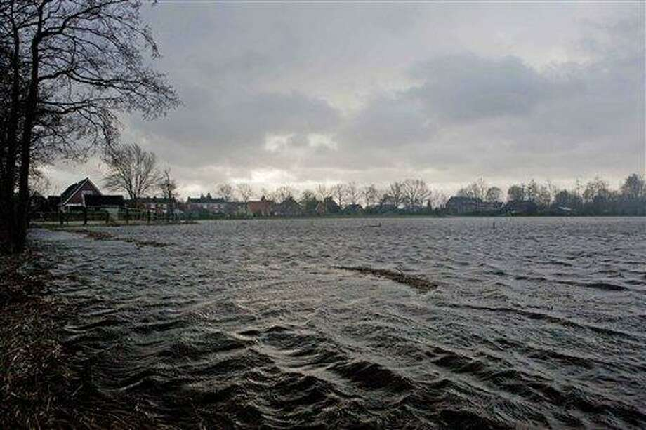 Farm land is inundated by flood water around the village of Boerakker, rear, northern Netherlands, Thursday. Farmers were told to evacuate a village in the Netherlands' low-lying north after days of driving rain and strong winds sparked fears of a dike breach. Authorities also cordoned off river banks in some areas of the densely populated south, distributing sandbags in flood-prone regions as the Netherlands resumed its never-ending battle to stay dry. A quarter of the country of nearly 17 million people lies below sea level, and 55 percent is considered vulnerable to flooding, according to the nation's Environmental Assessment Agency. (AP Photo/Peter Dejong) Photo: AP / AP