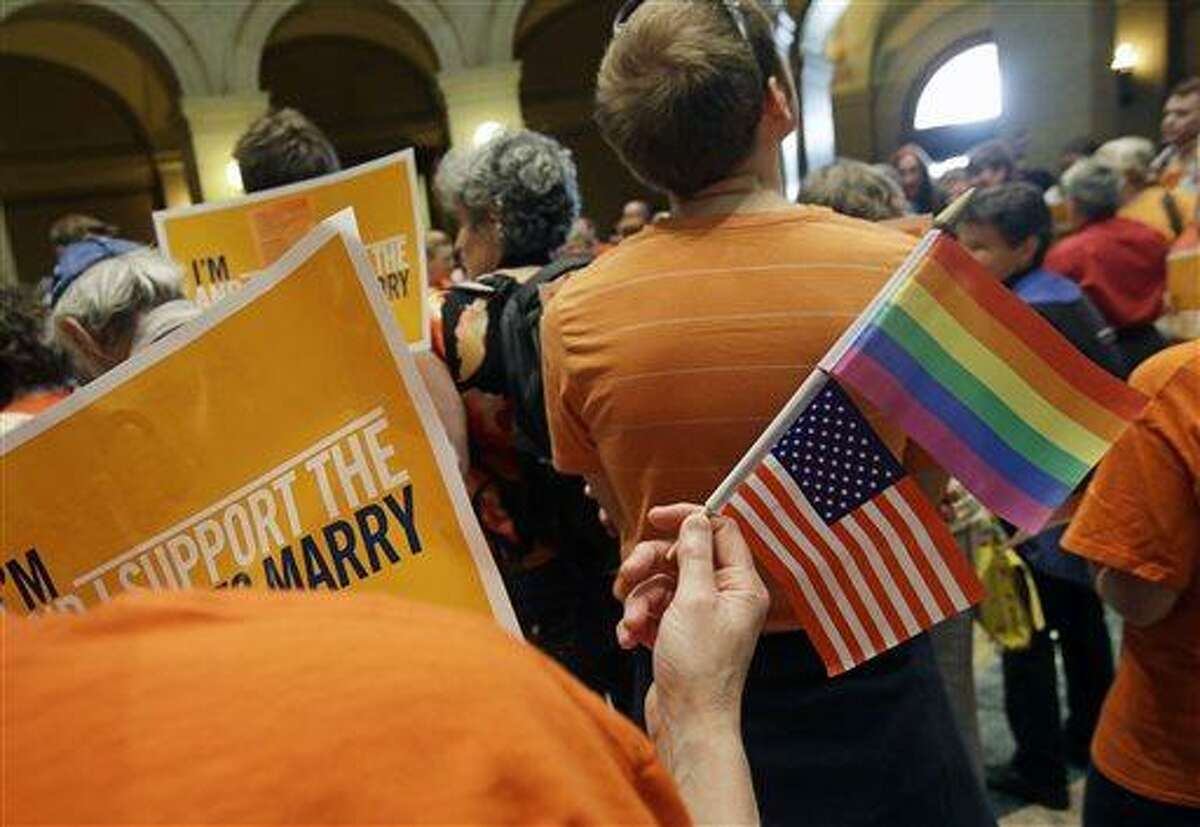A gay marriage supporter waves the U.S. flag and a rainbow flag as supporters and opponents of Minnesota's gay marriage bill gather in the State Capitol Rotunda in St. Paul as the Senate prepared to take up the issue Monday, May 13, 2013 in St. Paul, Minn. The bill passed the Minnesota House last week. (AP Photo/Jim Mone)