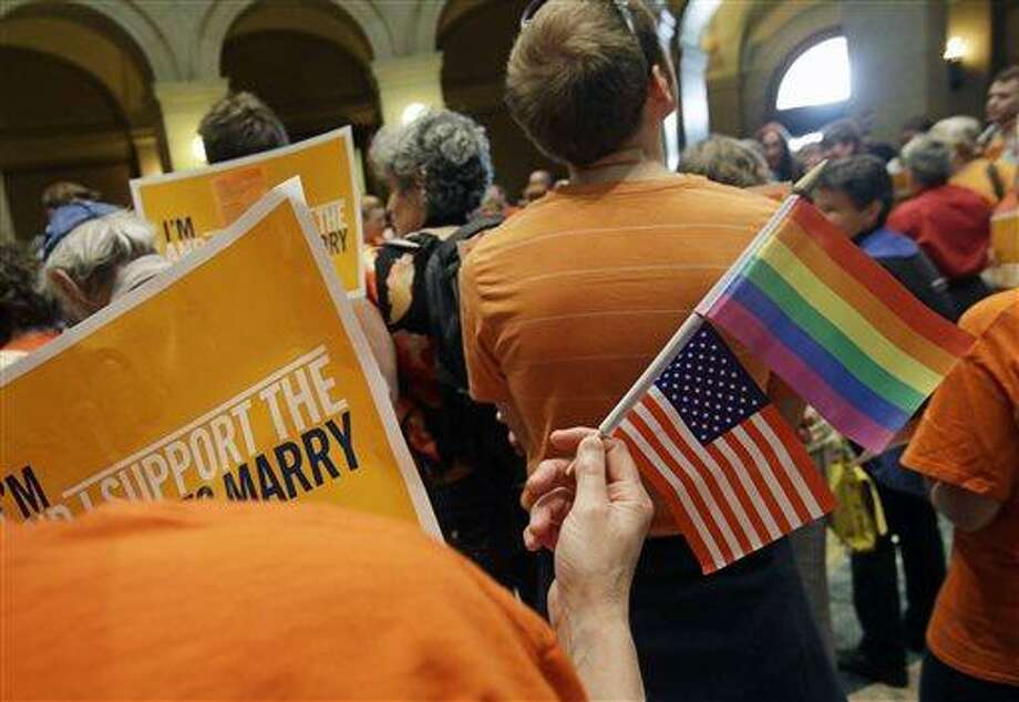 A gay marriage supporter waves the U.S. flag and a rainbow flag as supporters and opponents of Minnesota's gay marriage bill gather in the State Capitol Rotunda in St. Paul as the Senate prepared to take up the issue Monday, May 13, 2013 in St. Paul, Minn. The bill passed the Minnesota House last week. (AP Photo/Jim Mone) Photo: AP / AP