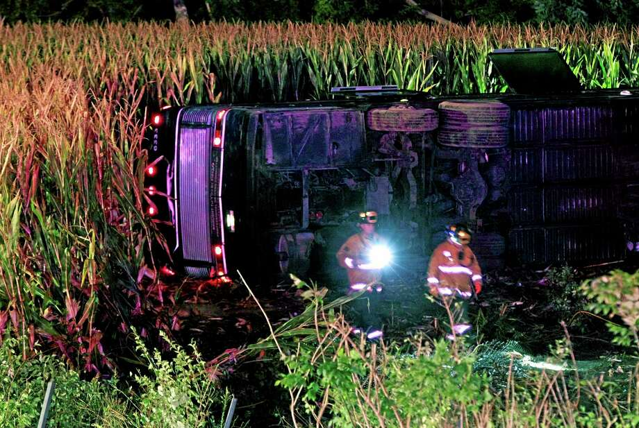 Officials work the scene of an overturned Greyhound bus on interstate I-75 in Liberty Township, Ohio on Saturday, Sept. 14, 2013. Authorities say that at least 34 people have been hurt, with injuries ranging from minor to severe. (AP Photo/Dayton Daily News, Nick Daggy) Photo: AP / Dayton Daily News