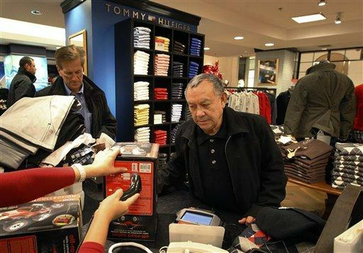 Jesus Esparza, right, of Chicago, shops at Macy's in Chicago in December 2011. Many retailers are reporting solid sales gains for December, capping a decent holiday season. Associated Press