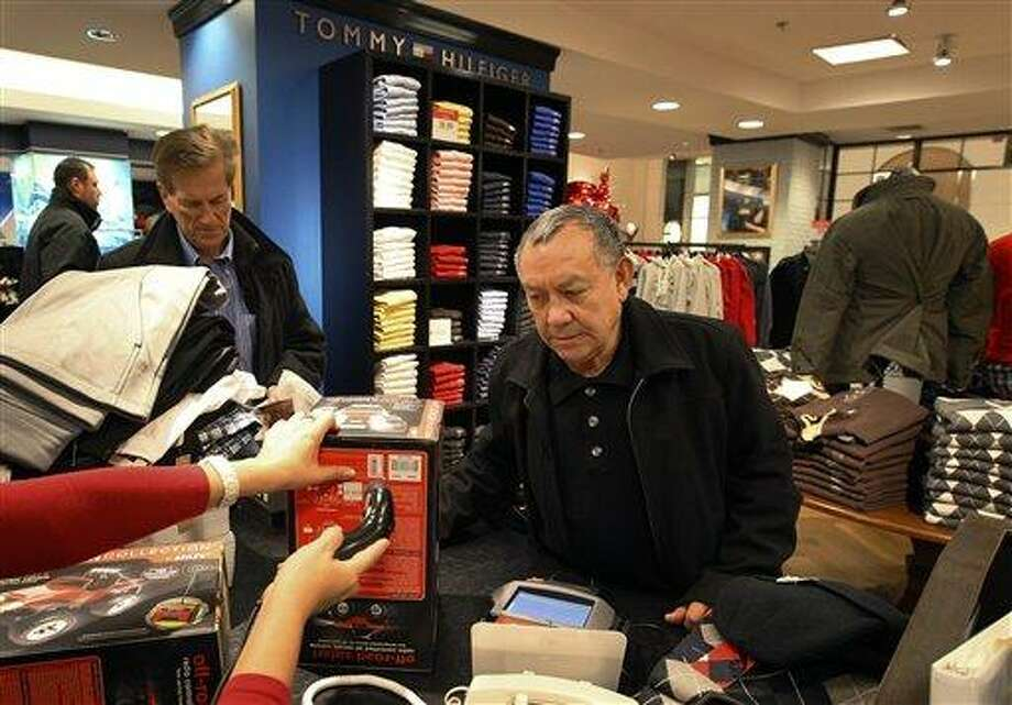 Jesus Esparza, right, of Chicago, shops at Macy's in Chicago in December 2011. Many retailers are reporting solid sales gains for December, capping a decent holiday season. Associated Press Photo: AP / AP