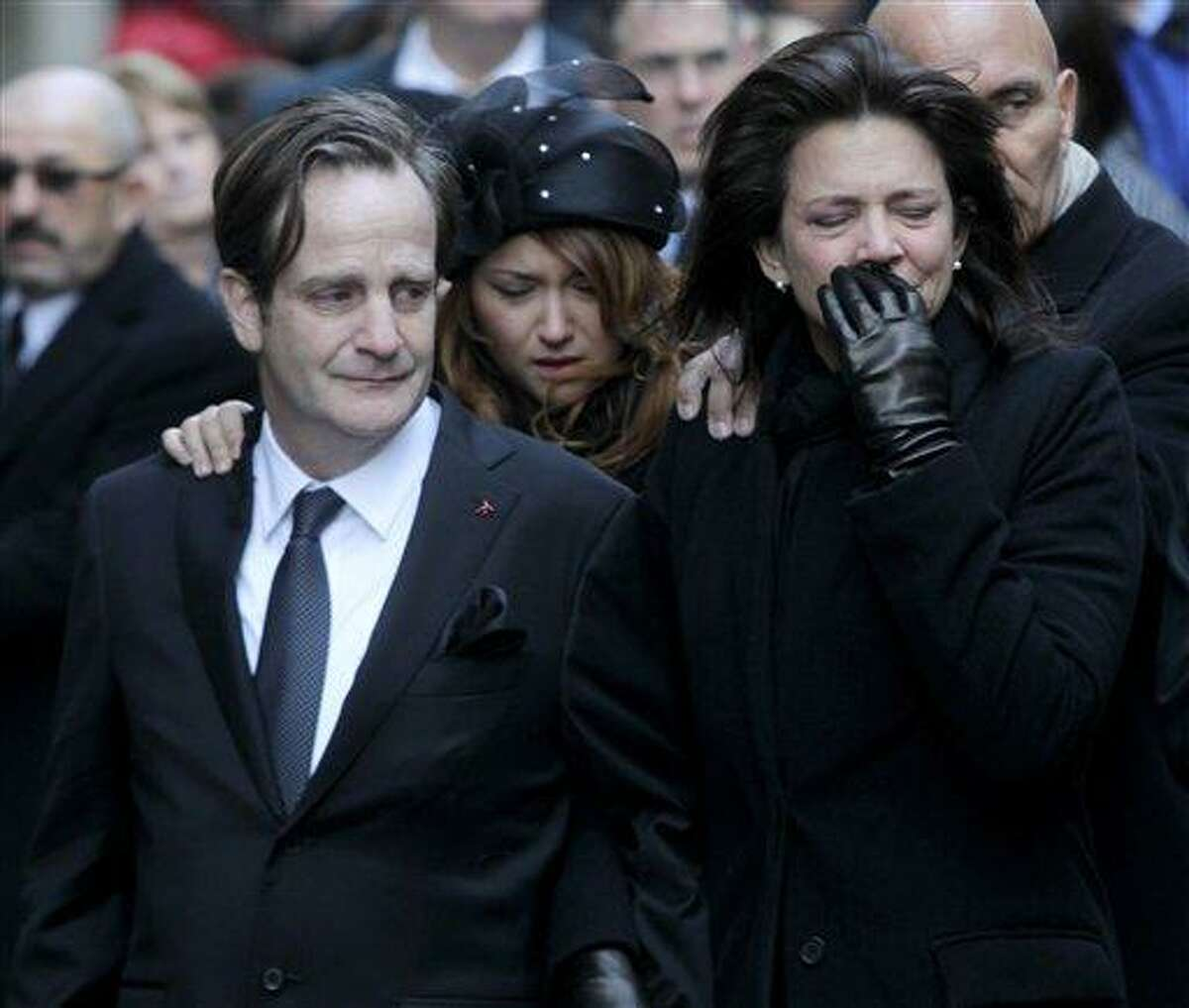 Matthew Badger, left, and Madonna Badger, the parents of three children that were killed in a fire, react as their caskets are carried into a church during the funeral in New York Thursday. Associated Press