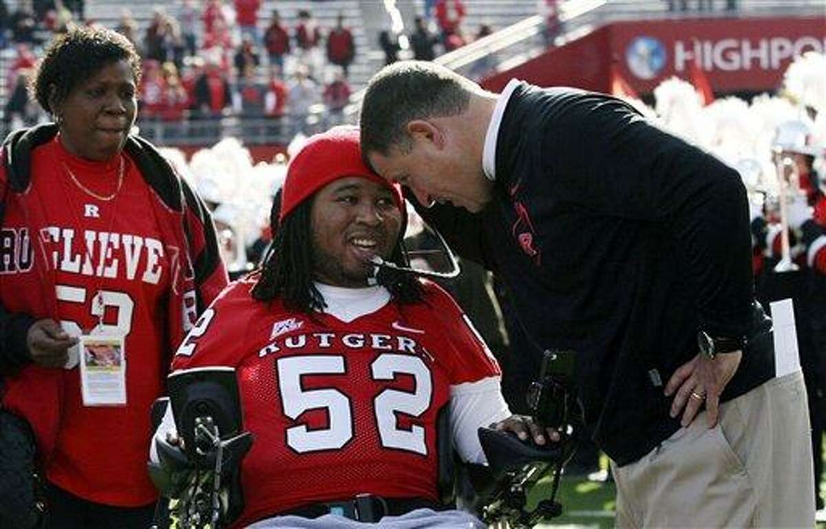 In this Nov. 19, 2011 file photo, paralyzed former Rutgers football player Eric LeGrand, center, is greeted by coach Greg Schiano, right, before an NCAA college football game against Cincinnati in Piscataway, N.J. Eric's mother, Karen LeGrand, looks on at left. LeGrand has been signed by the Tampa Bay Buccaneers. LeGrand broke two vertebrae and suffered a serious spinal cord injury on Oct. 16, 2010 during a kickoff return against Army. His coach at Rutgers then, now is coach of the Bucs. Associated Press