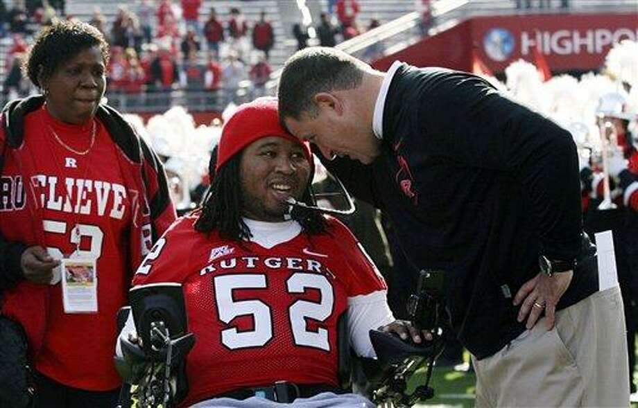 In this Nov. 19, 2011 file photo, paralyzed former Rutgers football player Eric LeGrand, center, is greeted by coach Greg Schiano, right, before an NCAA college football game against Cincinnati in Piscataway, N.J. Eric's mother, Karen LeGrand, looks on at left. LeGrand has been signed by the Tampa Bay Buccaneers. LeGrand broke two vertebrae and suffered a serious spinal cord injury on Oct. 16, 2010 during a kickoff return against Army. His coach at Rutgers then,  now is coach of the Bucs. Associated Press Photo: AP / AP2011