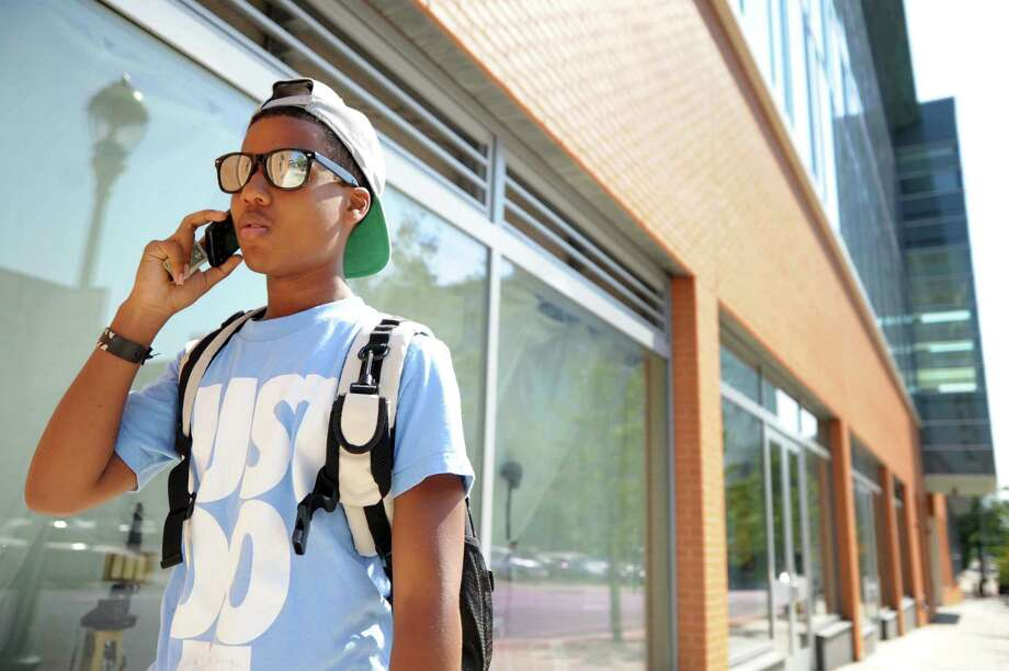 Cameron Twitty, a senior from New Haven, talks on his cell phone outside of Coop High School on College Ave Friday afternoon August 31, 2012
