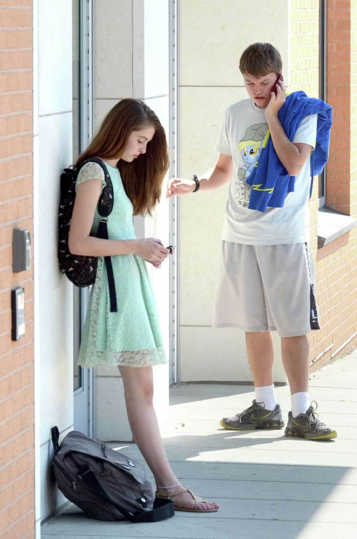 Coop High School Tenth graders Ilana Zsigmond and Tyler Ambrose, both of Hamden use their phones after school August 31, 2012 on College Ave in New Haven. vmWilliams