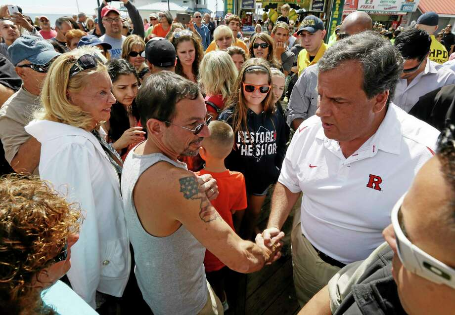 Pete Bachella, center left, of Ringwood, N.J., displays his New Jersey map tattoo to New Jersey Gov. Chris Christie during a visit to the Seaside Park boardwalk two days after a massive fire burn a large portion of the boardwalk, Saturday, Sept. 14, 2013, in Seaside Park, N.J. The fire, which apparently started in an ice cream shop and spread several blocks, hit the recently repaired boardwalk, which was damaged by Superstorm Sandy in 2012. There were no reports of any injuries. Photo: Julio Cortez — The Associated Press  / AP