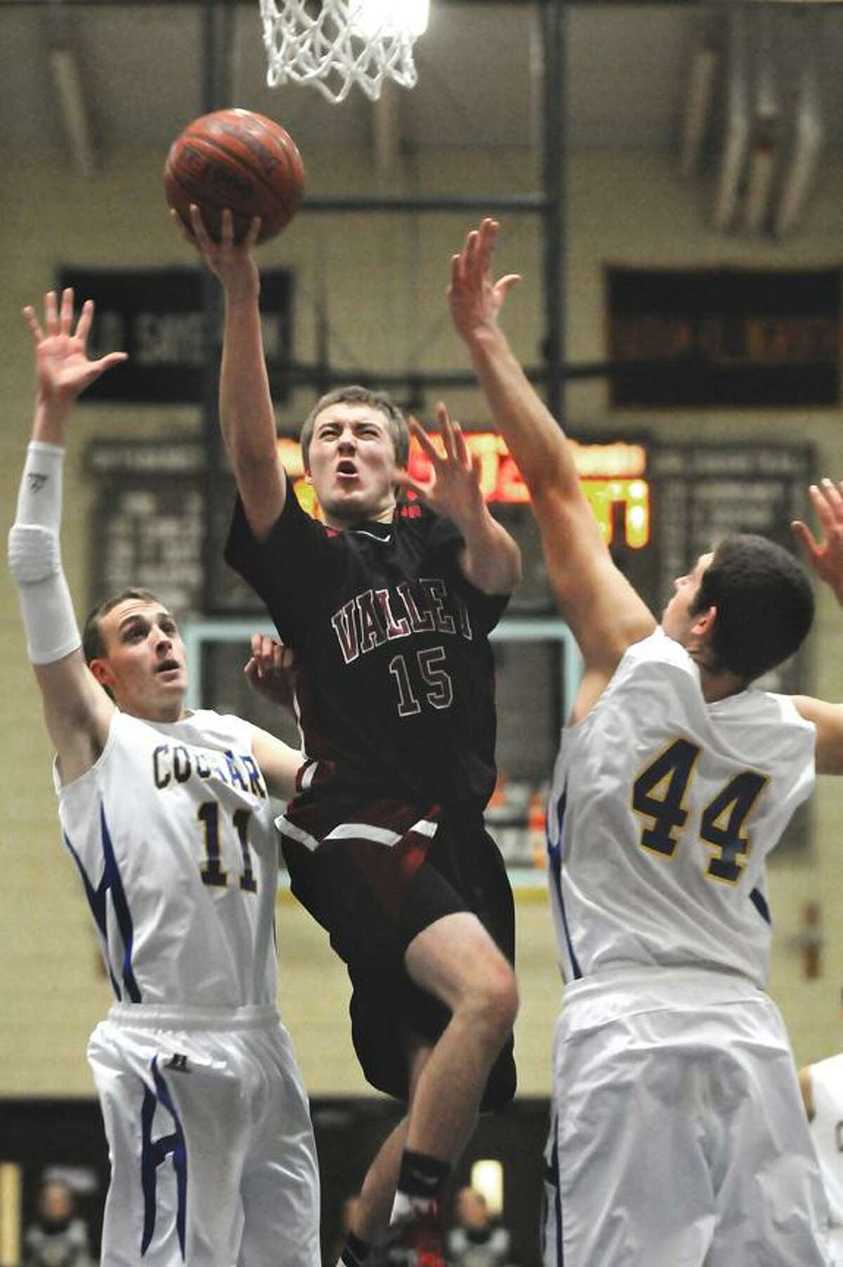 The Middletown Press 15.12 Haddam-Killingworth senior guard/forward Erik Carlson stuffs Valley's Mason King Thursday evening at the H-K Field House. The Cougars defeated Valley 84-73.