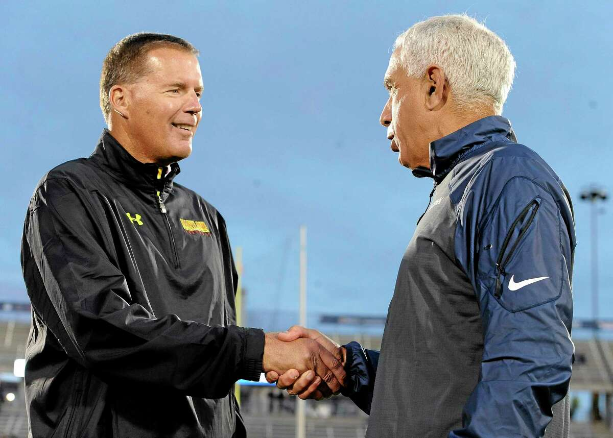 Maryland head coach Randy Edsall, left, shakes hands with UConn head coach Paul Pasqualoni before Saturday's game at Rentschler Field.