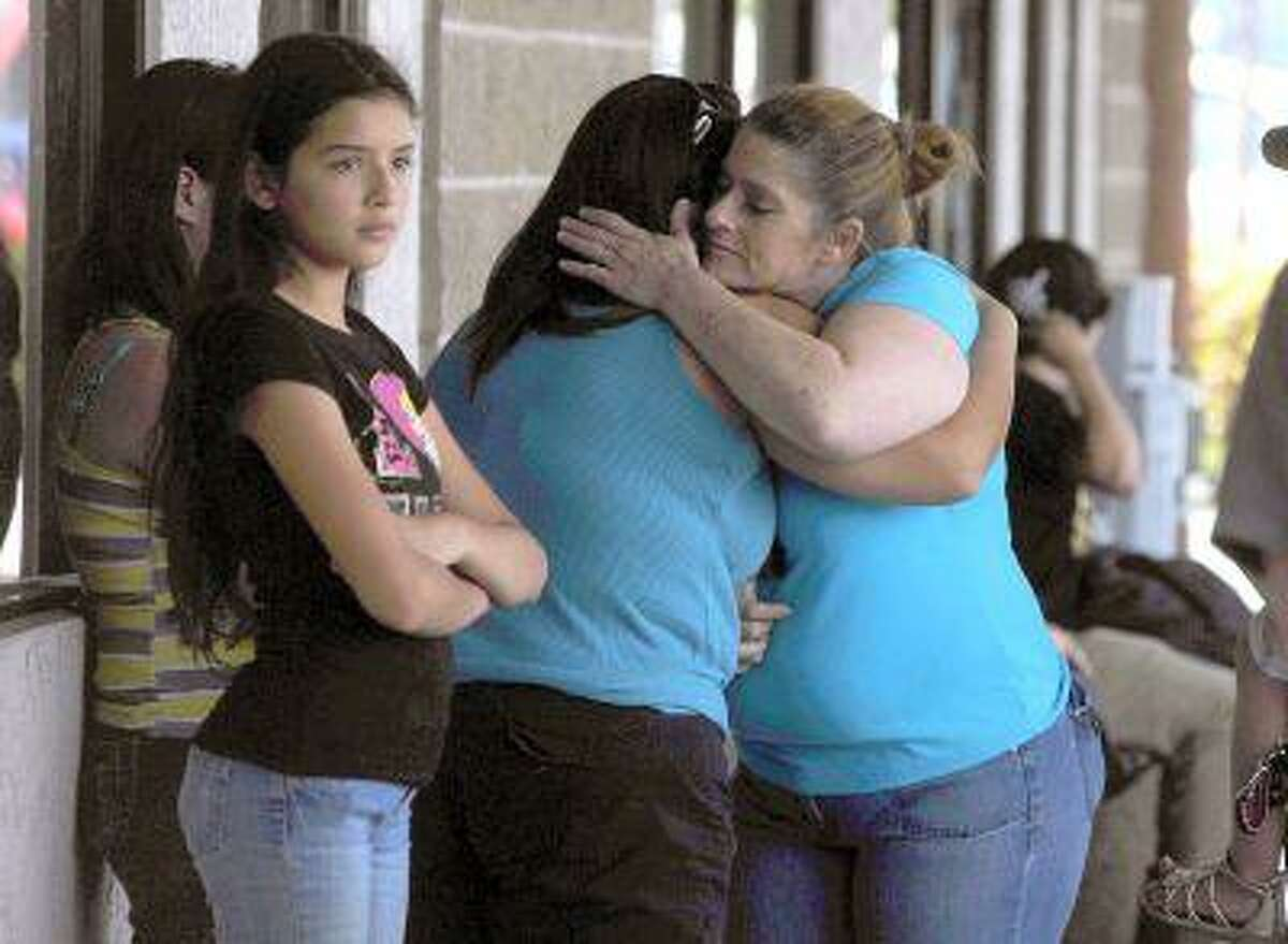 In a Sunday, April 28, 2013 photo, Valley Springs residents Stacey Sims, right, comforts fellow resident Amanda Pekarek, who both knew the 8 year old murder victim Leila Fowler, who was friends with their children, after a press conference outside the Sheriff's substation in Valley Springs on Sunday.