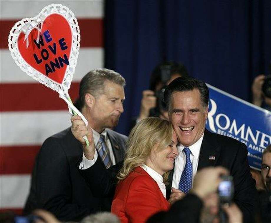 """Ann Romney hugs her husband Republican presidential candidate, former Massachusetts Gov. Mitt Romney as he holds a """"We Love Ann"""" sign during a Romney for President Iowa Caucus night rally in Des Moines, Iowa, Tuesday, Jan. 3, 2012. (AP Photo/Charlie Neibergall) Photo: AP / AP"""
