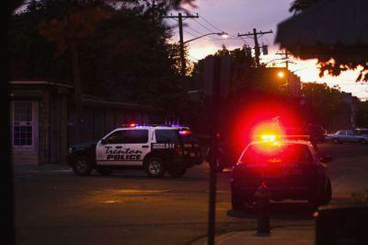 Police cars are parked near a house, where an armed man with multiple hostages remain barricaded in, in Trenton, New Jersey, May 11, 2013.