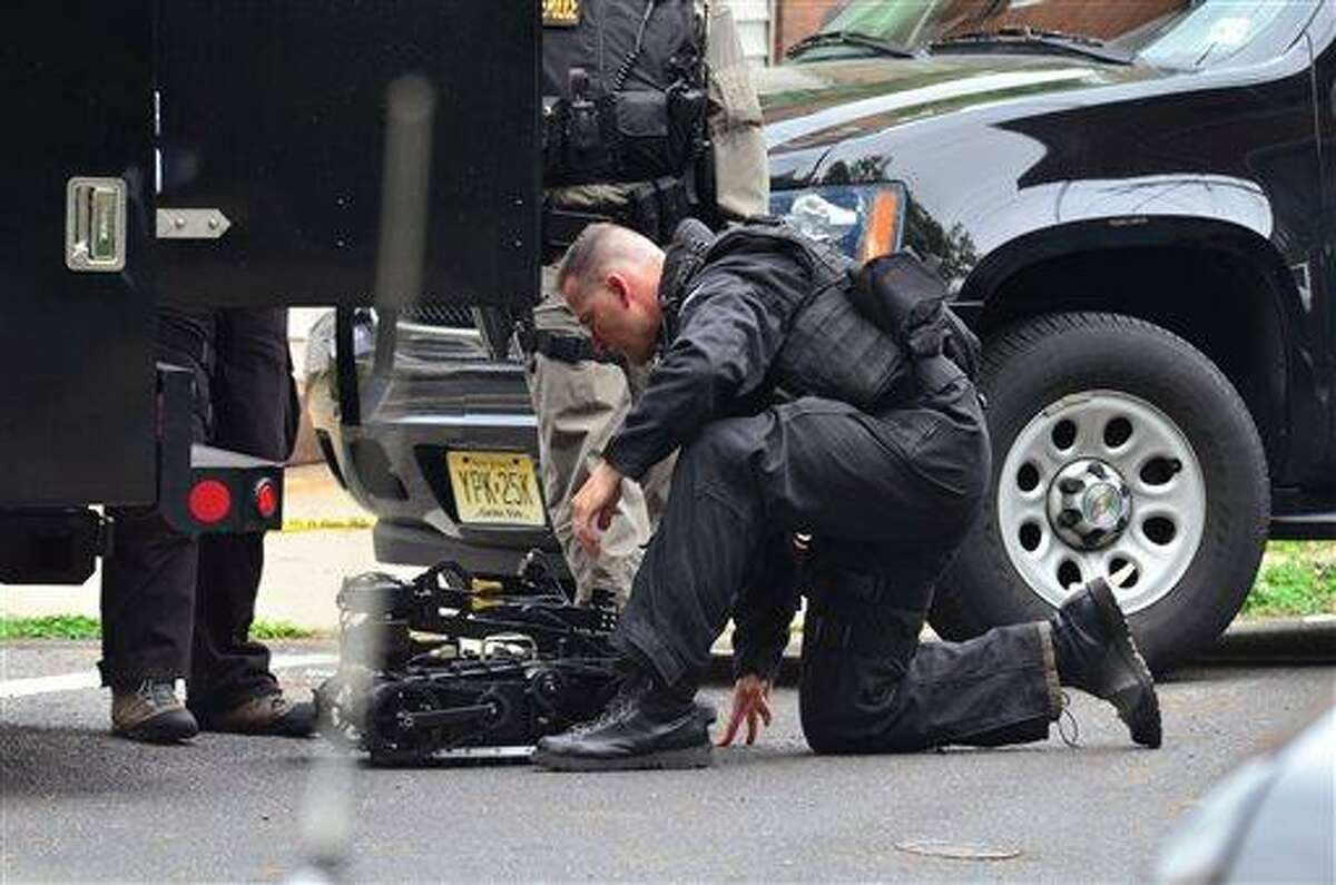 A state police swat team member readies a robot to enter a home where a man had barricaded himself on Friday, May 10, 2013 in Trenton, N.J. The standoff with an armed man who police said took multiple hostages entered its second day Saturday as authorities worked to negotiate his surrender and his captives' safe release. The man, whose identity has not been released, was holed up in a brick house in South Trenton more than 18 hours after the standoff began Friday afternoon, authorities said. (AP Photo/The Trentonian, Scott Ketterer) TRENTON TIMES OUT; PHILLY METRO OUT