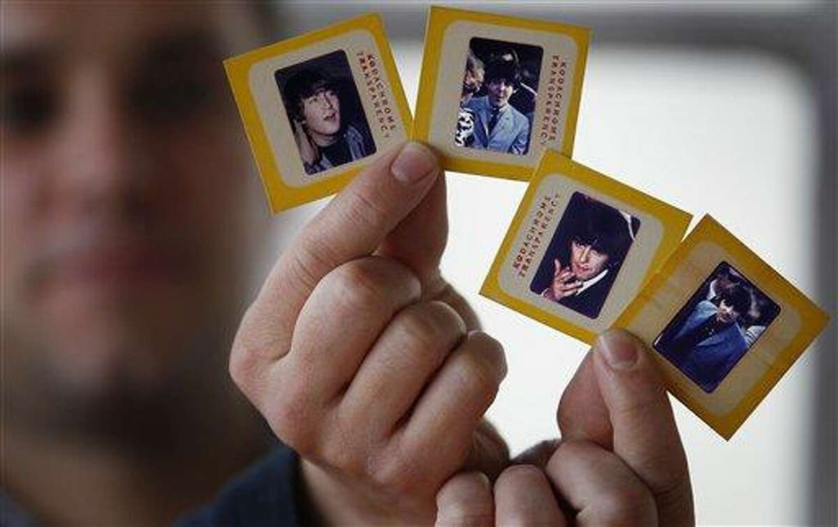 Auctioneer Paul Fairweather holds four colour transparencies of The Beatles taken during their first tour of the USA in 1964. The rare colour transparencies, taken by Dr. Robert Beck, are to be sold along with the copyright at Omega Auctions in Stockport, England, in a special Beatles memorabilia auction in March 2013. The unpublished collection of 65 slides contain many stage shots.AP Photo