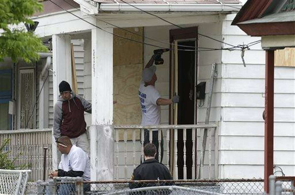 Workers board up the house Saturday, May 11, 2013 where three women were held in Cleveland on Saturday, May 11, 2013. Suspect Ariel Castro, who allegedly held three women captive for nearly a decade, is charged with rape and kidnapping. (AP Photo/Tony Dejak)