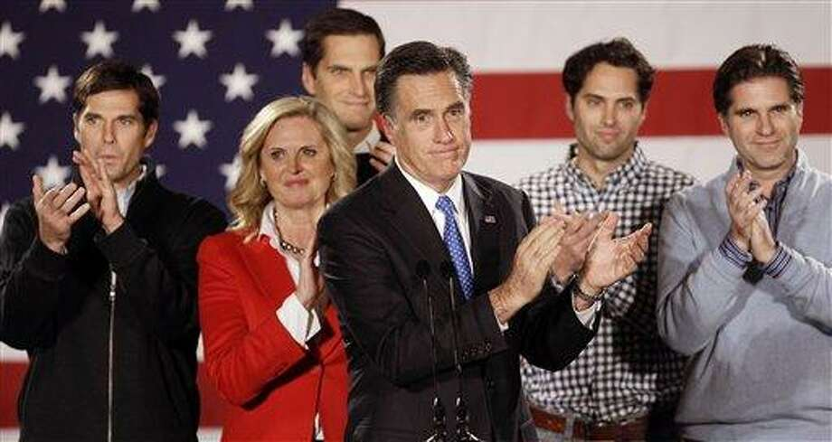 Republican presidential candidate, former Massachusetts Gov. Mitt Romney applauds after addressing a crowd of supporters with his wife Ann and their sons Matt, Josh, Craig and Tagg behind him during a Romney for President Iowa Caucus night rally in Des Moines, Iowa, Tuesday. Associated Press Photo: AP / AP