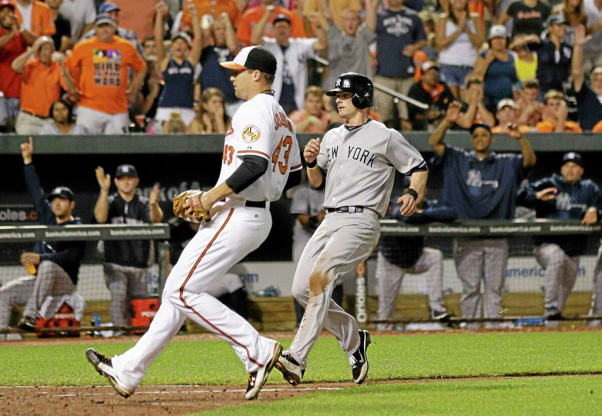 The Yankees' Brendan Ryan, right, runs toward home plate for a run past Orioles relief pitcher Jim Johnson after Johnson threw a wild pitch in the ninth inning Thursday.
