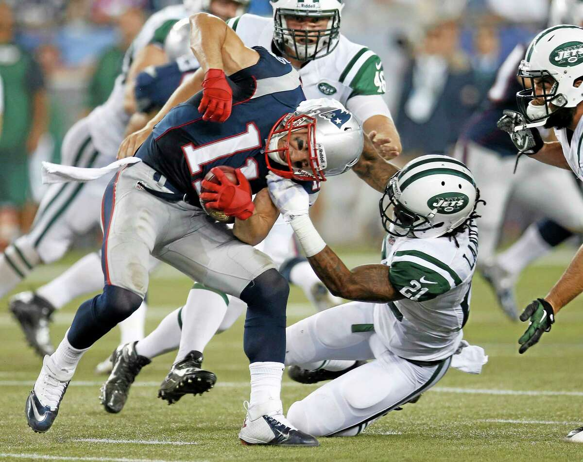 Jets defensive back Ellis Lankster (21) tries to tackle Patriots receiver Julian Edelman during the second quarter Thursday.