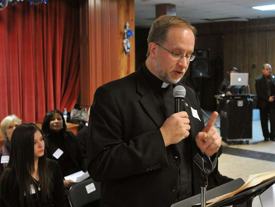 Reverend James Manship speaks to the crowd at the St. Rose's of Lima church supporting a driver's license program for undocumented immigrants in CT. Photo-Peter Casolino