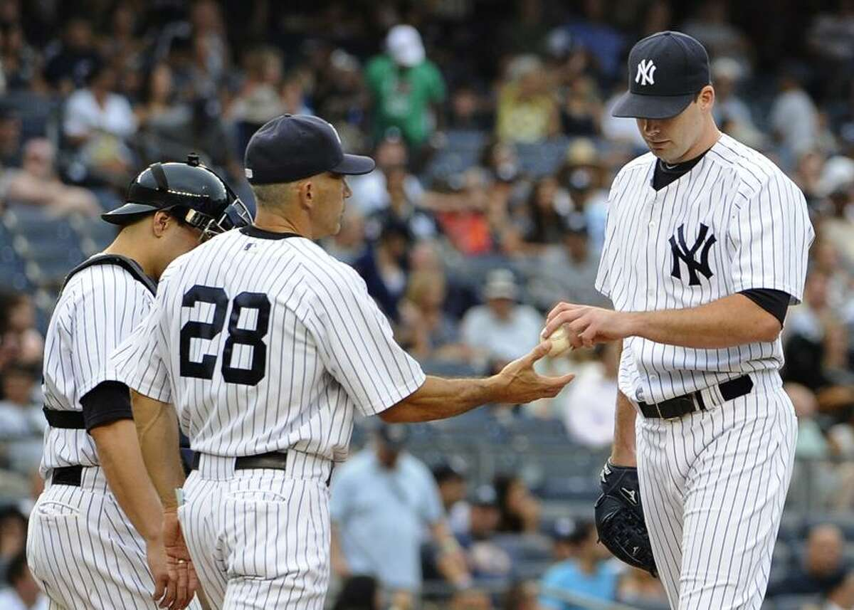 New York Yankees catcher Russell Martin, left, looks on as manager Joe Girardi (28) takes Boone Logan out of the baseball game after Baltimore Orioles' Nick Markakis hit a two-run single in the eighth inning on Sunday, Sept. 2, 2012, at Yankee Stadium in New York. (AP Photo/Kathy Kmonicek)