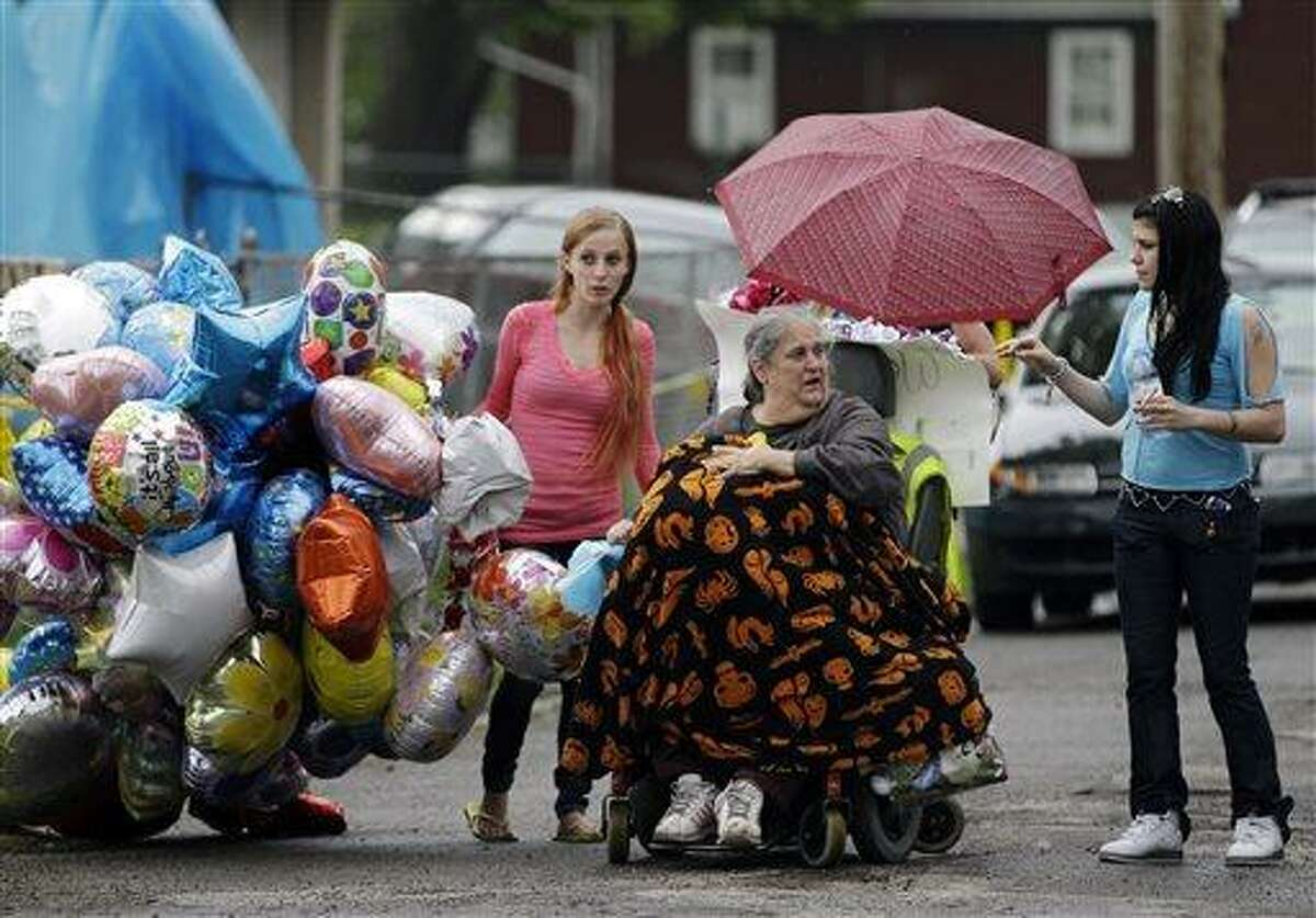 Deborah Knight, center, grandmother of Michelle Knight, drives her wheelchair past the home of Gina DeJesus in Cleveland Friday, May 10, 2013. Michelle Knight was freed from the home of Ariel Castro along with DeJesus and Amanda Berry Monday where the 52-year-old man had held them captive for a decade. (AP Photo/Mark Duncan)