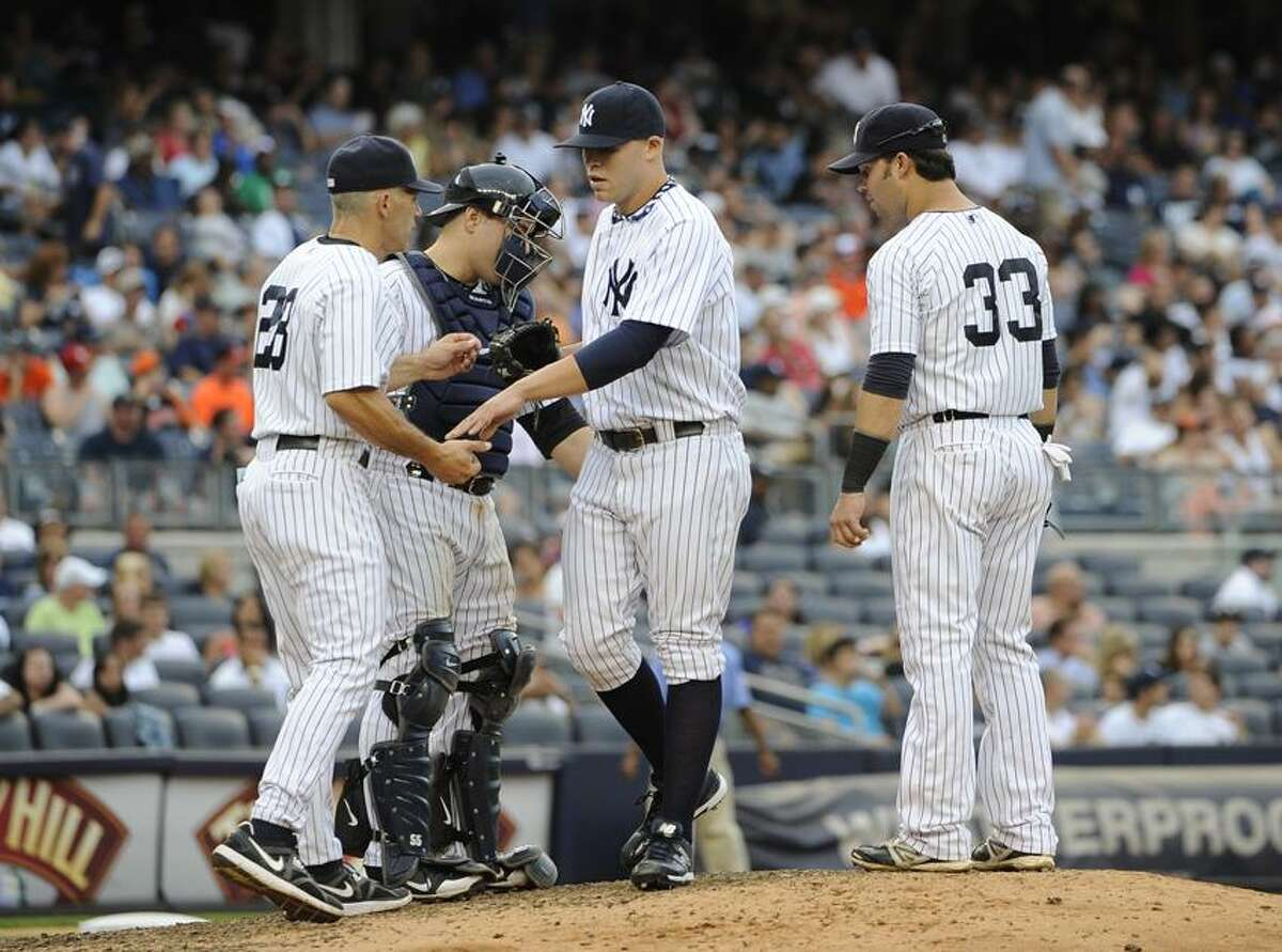 New York Yankees catcher Russell Martin, second from left, and Nick Swisher (33) watch manager Joe Girardi take Justin Thomas out against the Baltimore Orioles in the eighth inning of a baseball game on Sunday, Sept. 2, 2012, at Yankee Stadium in New York. The Orioles won 8-3. (AP Photo/Kathy Kmonicek)