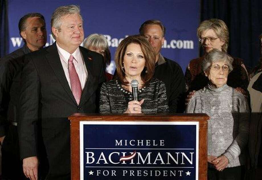 Rep. Michele Bachmann, R-Minn., center, joined by husband, Marcus, left, family and friends, announces that she will end her campaign for president Wednesday in West Des Moines, Iowa. Associated Press Photo: AP / AP