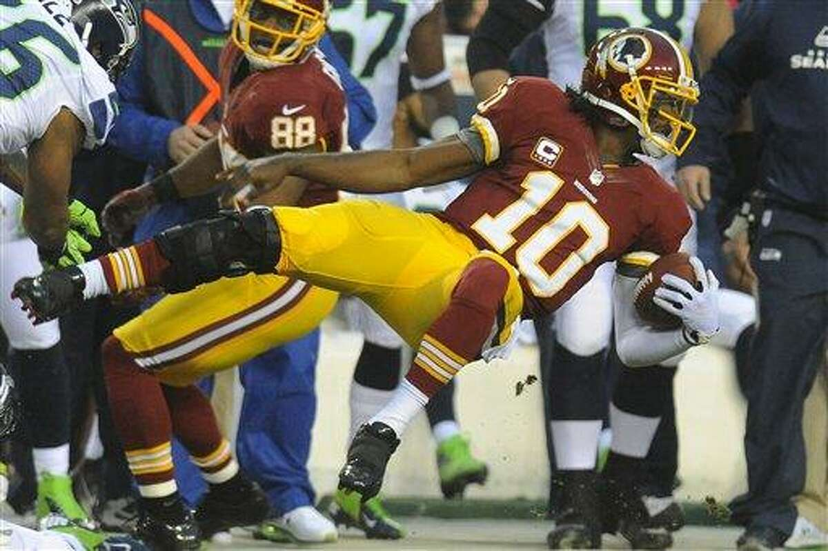 Washington Redskins quarterback Robert Griffin III flies through the air as he is knocked out of bounds during the first half of an NFL wild card playoff football game against the Washington Redskins in Landover, Md., Sunday, Jan. 6, 2013. (AP Photo/Richard Lipski)