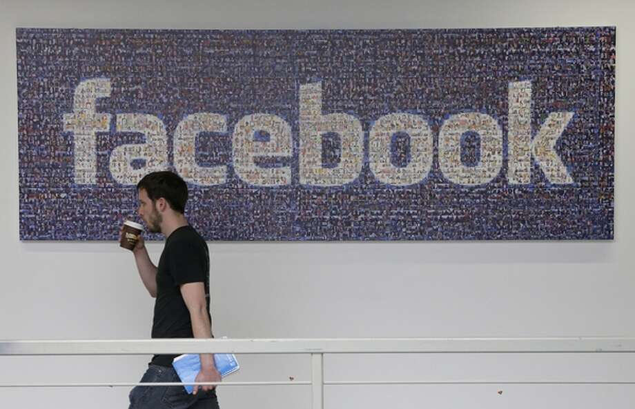 FILE - In this March 15, 2013 file photo, a Facebook employee walks past a sign at Facebook headquarters in Menlo Park, Calif. Facebook and Yahoo on Monday, Sept. 9, 2013 asked a secret court to allow them to disclose data on national security orders the companies have received under the Foreign Intelligence Surveillance Act. (AP Photo/Jeff Chiu, File) Photo: AP / AP net