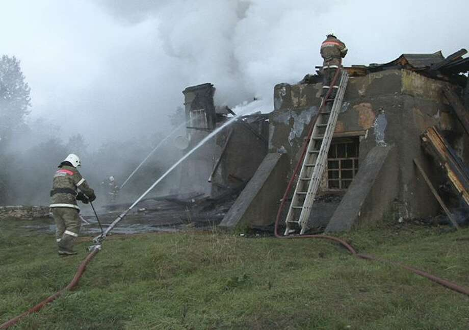 In this photo released by the Novgorod region branch of Russian Emergency Ministry, the ministry's Emergency Situations workers and fire fighters work at a site of a fire at a psychiatric hospital in Luka village in the Novgorod region, Russia, early Friday, Sept. 13, 2013. A fire swept through the Russian psychiatric hospital overnight, killing at least three people and leaving more than 30 others feared dead, officials said Friday. Authorities had long warned that the building was unsafe and called for its closure. (AP Photo/Russian Emergency Ministry, the Novgorod region branch) Photo: AP / Russian Emergency Ministry
