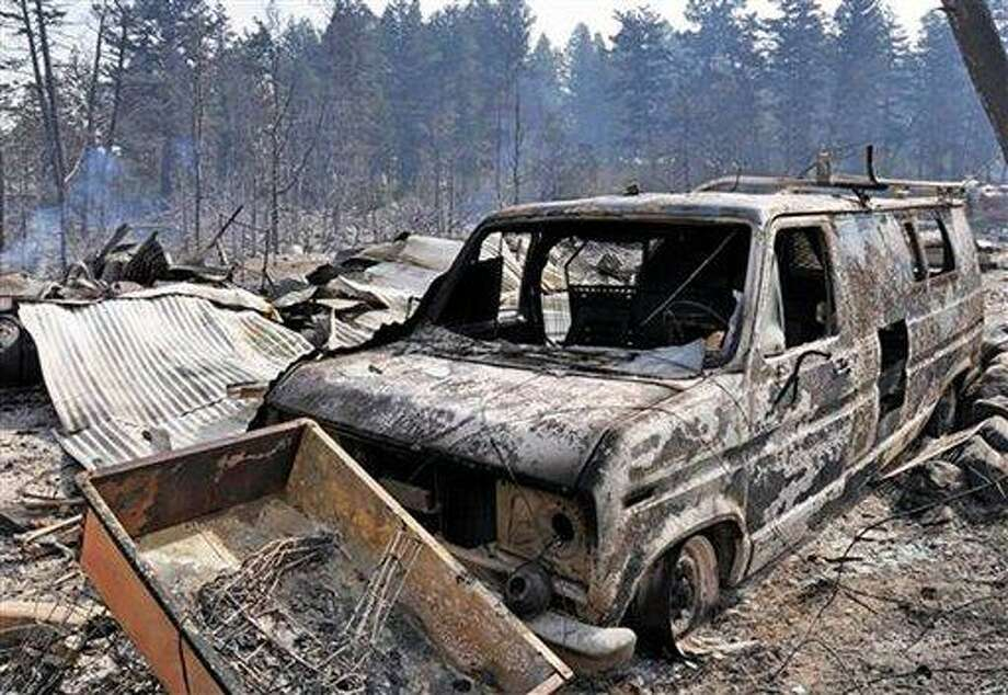 A burned area and vehicle from the Pine creek fire are shown Friday Aug. 31, 2012, near Livingston, Mont. The Pine Creek Fire south of Livingston has grown to almost 19 square miles and burned at least five homes. Evacuations were still in effect but were being eased in areas where the flames have died down. (AP Photo/Livingston Enterprise, Shawn Raecke) Photo: AP / Livingston Enterprise