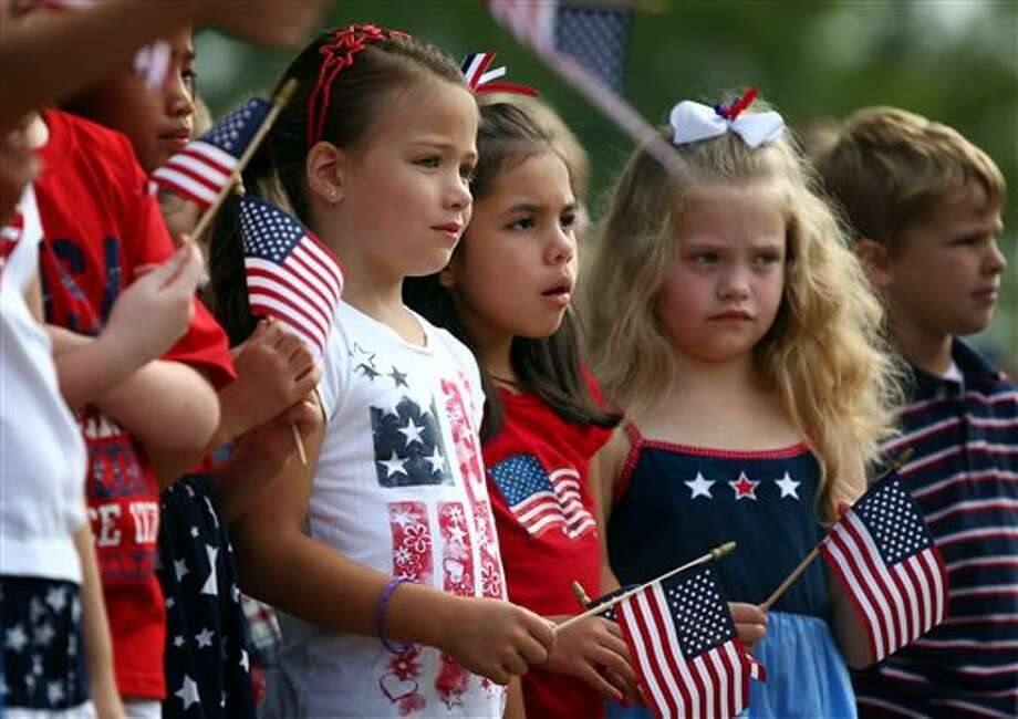Fom left, Altruria Elementary students Kate Switzer, Gaby Aguilar, Gracie David, and John Sanders participate in the school's annual Altruria Elementary School Remembers ceremony in honor of 9/11 terrorist attacks in Bartlett, Tenn. Wednesday, Sept. 11, 2013. The students gathered for a moment of silence, a flag presentation, the Pledge of Allegiance and National Anthem.  (AP Photo/The Commercial Appeal, Nikki Boertman) Photo: AP / The Commercial Appeal