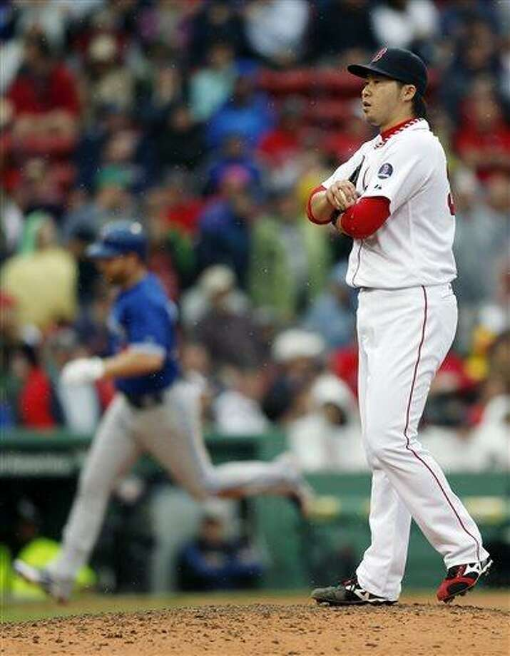 Boston Red Sox's Junichi Tazawa stands on the mound after giving up a solo home run to Toronto Blue Jays' Adam Lind, left, in the ninth inning of a baseball game in Boston, Saturday, May 11, 2013. The Blue Jays won 3-2. (AP Photo/Michael Dwyer) Photo: AP / AP