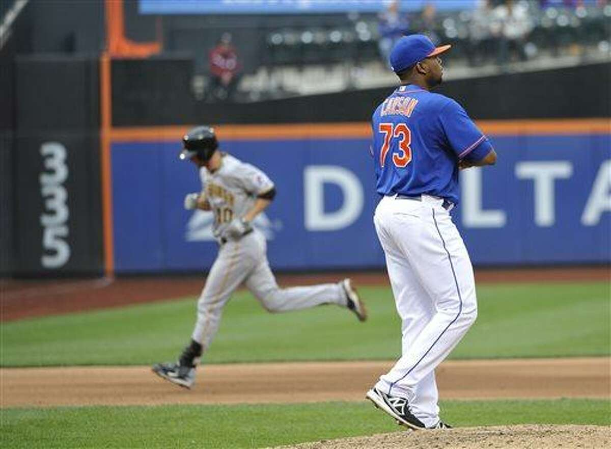 New York Mets relief pitcher Robert Carson (73) reacts on the mound as Pittsburgh Pirates' Jordy Mercer rounds the bases after hitting a solo home run in the eighth inning of a baseball game at Citi Field on Saturday, May 11, 2013 in New York. Mercer hit two home runs in the Pirates 11-2 win. (AP Photo/Kathy Kmonicek)